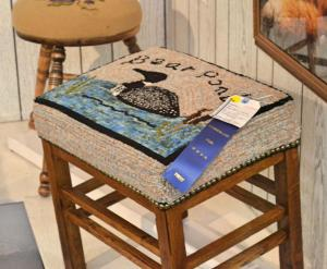 Irene's Bear Pond loon foot stool was selected as one of the Best in Show items!  Design by Parris House Wool Works.
